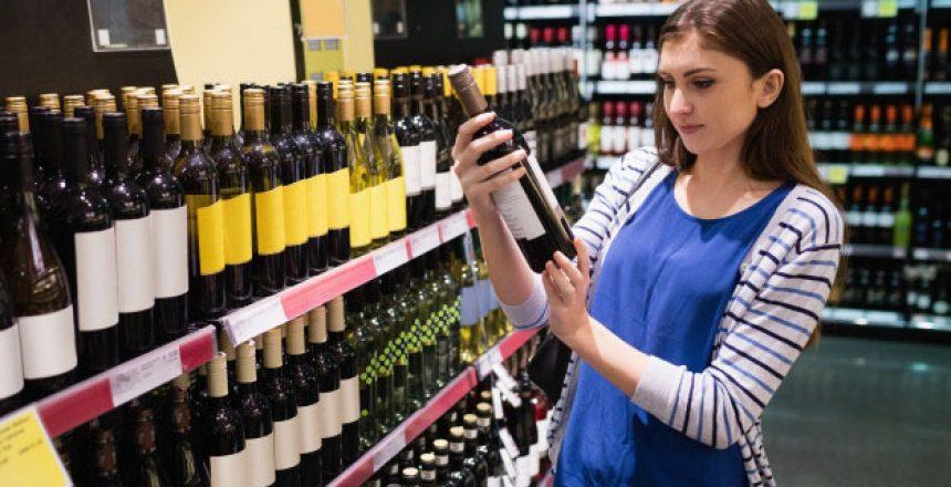 woman-looking-wine-bottle cropped